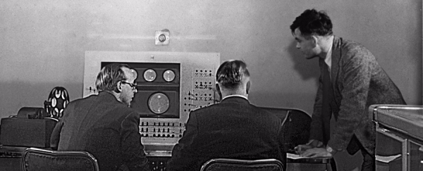 Turing (standing) at the Ferranti Mark I console (Courtesy of the University of Manchester School of Computer Science)